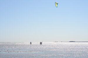 Elev och lärare övar kitekontroll i långgrunt vatten.